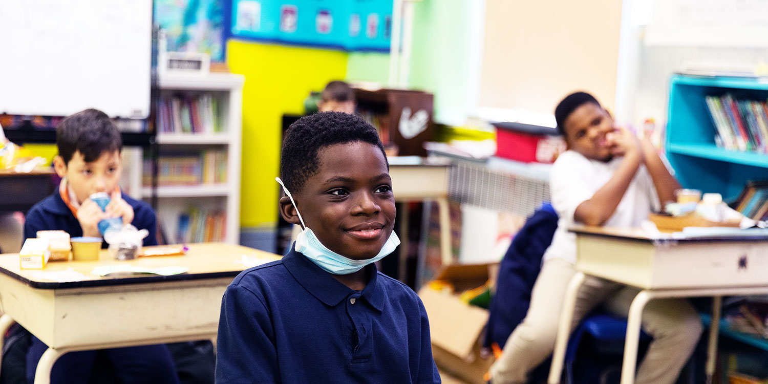 Smiling elementary student at their desk.