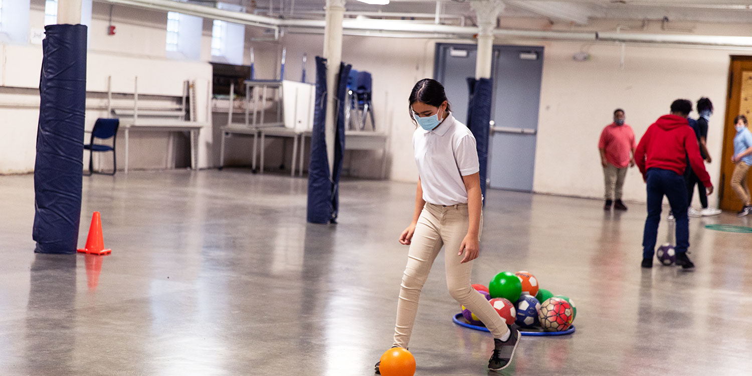 Student kicking a soccer ball during gym class.