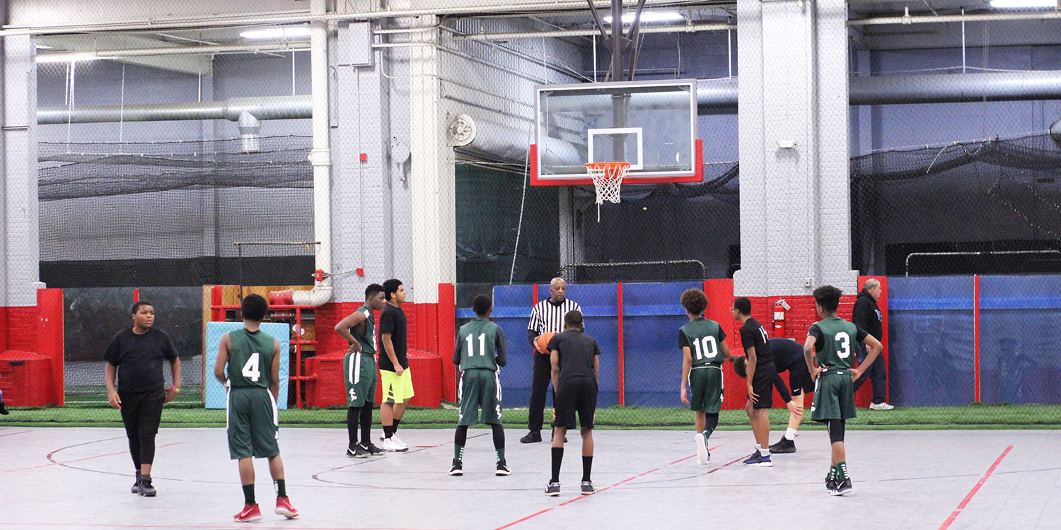 Students playing in a competitive basketball game.